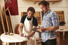 Carpenter With Apprentice Making Bespoke Wooden Surfboard Stock Photos