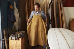 Carpenter Putting Apron On In Bespoke Surfboard Workshop Stock Photos