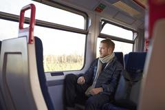 Young Man Sitting In Train Carriage On Railway Journey Stock Photos