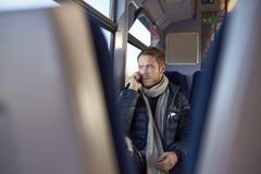 Man Sitting In Train Carriage Talking On Mobile Phone - stock photo