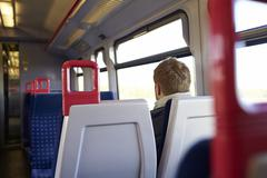 Rear View Of Man Sitting In Train Carriage On Rail Journey - stock photo