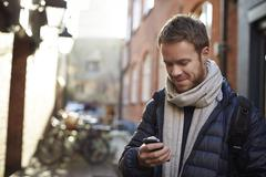 Man Uses Mobile Phone To Navigate Route Through City Streets - stock photo