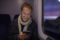 Man Sitting In Train Carriage Sending Text Message - stock photo