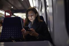 Woman Sitting In Train Carriage Sending Text Message - stock photo