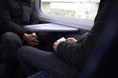 Man Sitting In Train Carriage Looking At Text Message - stock photo