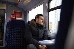 Young Man Sitting In Train Carriage On Railway Journey - stock photo