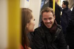 Young Couple Sitting In Train Carriage On Railway Journey Stock Photos