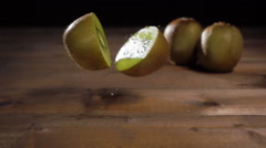 Kiwi falling on rustic wooden table slow motion Stock Footage