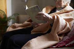 Senior Woman Sitting On Sofa Reading Book Wrapped In Blanket - stock photo