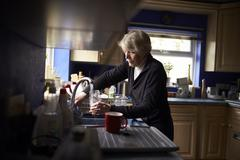 Senior Woman Doing Washing Up In Kitchen Stock Photos