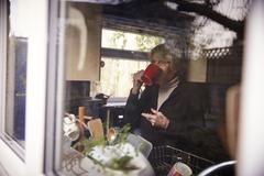 Senior Woman With Hot Drink In Kitchen Shot Through Window - stock photo