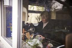 Senior Woman Making Hot Drink In Kitchen Shot Through Window - stock photo