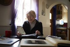 Senior Woman Looking Through Photo Album At Home - stock photo