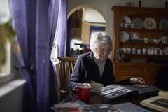 Senior Woman Looking Through Photo Album At Home Stock Photos