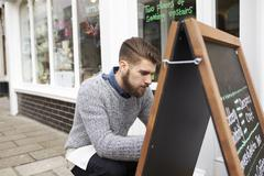 Man Writing On Noticeboard Outside Coffee Shop Stock Photos