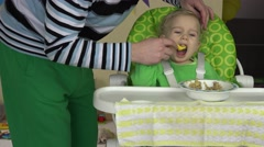 Father teaching his happy little cute baby to eat with spoon from bowl Stock Footage