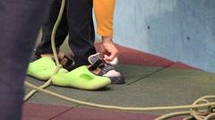 Woman wearing climbing shoes around artificial outdoor climbing wall Stock Footage