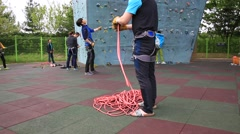 People holding ropes with safety block while climbers climbing on wall Stock Footage