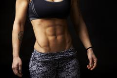 Mid-section crop shot of muscular young woman's abs and arms - stock photo