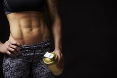 Mid-section crop of muscular young woman holding drink cup - stock photo