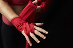 Woman wrapping hand for boxing training, hands to camera - stock photo