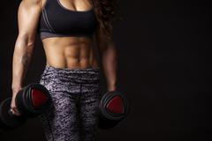Muscular woman working out with dumbbells, mid-section crop Stock Photos