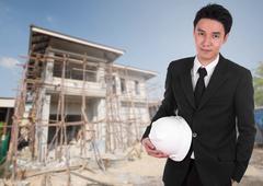 Engineer holding helmet with house construction background Kuvituskuvat