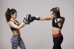 Young woman boxing training with her female sparring partner - stock photo