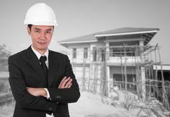 Engineer in helmet with arms crossed, house construction background Kuvituskuvat