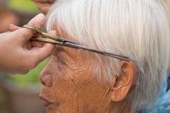 Cutting senior woman's gray hair Stock Photos