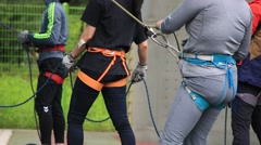 People holding ropes with safety block while climbers climbing Stock Footage