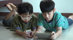 Young asian boys playing online games on tablet computer and smart phone Stock Footage