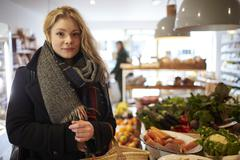 Portrait Of Woman Shopping For Produce In Delicatessen Stock Photos