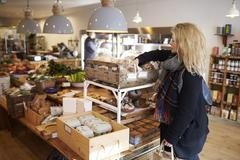 Woman Shopping For Organic Bread In Delicatessen - stock photo