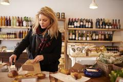 Woman Buying Baked Quiche In Delicatessen Stock Photos