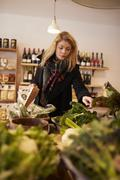 Woman Shopping For Organic Produce In Delicatessen - stock photo