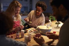 Family Sit Around Table And Decorate Cupcakes Together Stock Photos