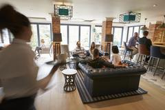 Busy Reception Area Of Modern Boutique Hotel With Guests - stock photo