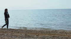 Lonely woman walking along the shore of beach with a bottle of wine Stock Footage