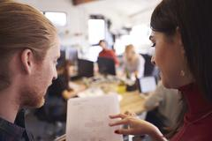 Two Designers Looking At Document In Busy Office Stock Photos