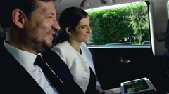 Beautiful business people in limousine laughing happy - stock footage