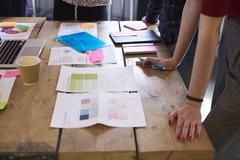 Close Up Of Designers Discussing Layouts And Color Schemes Stock Photos