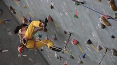 Teenage girl climbing on artificial outdoor climbing wall Stock Footage