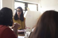 Female Manager Leads Meeting Around Table In Design Office - stock photo
