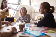 Female Manager Leads Meeting Around Table In Design Office Stock Photos