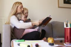 Mother Sitting On Sofa Reading Story With Daughters Stock Photos