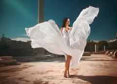 Ethereal, divine bride with flying, shiny dress standing in temple ruins. Stock Photos
