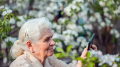 Senior woman shoots video on tablet Stock Footage