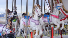 Pan left to merry-go-round horses in public park. Stock Footage