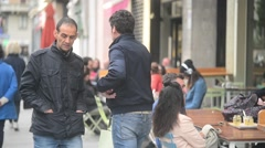 People walk and sitting relax at street cafe in center of Milan city spring Stock Footage